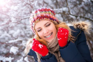 Girl with braces smiling in snow